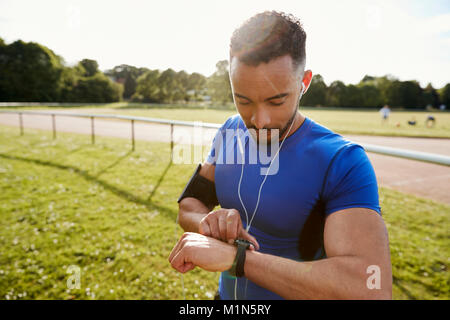 Young man at running track setting fitness app on smartwatch - Stock Photo
