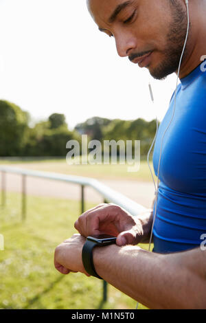 Male athlete at running track setting smartwatch app - Stock Photo