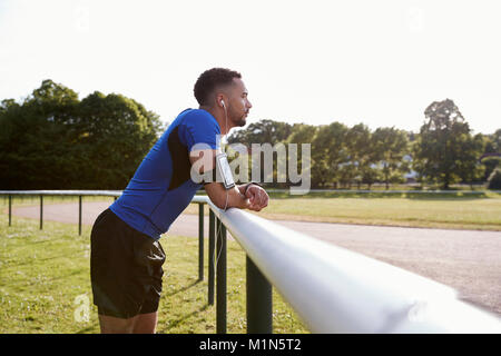 Male athlete at track leaning on fence, three quarter length - Stock Photo