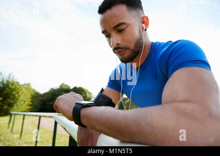 Male athlete at track checking smartwatch app, close up - Stock Photo