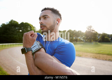 Male athlete at track stretching shoulders, close up - Stock Photo