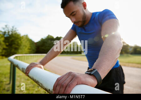 Male athlete leaning on fence at running track, close up - Stock Photo