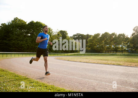 Young male athlete running at a track, full length - Stock Photo