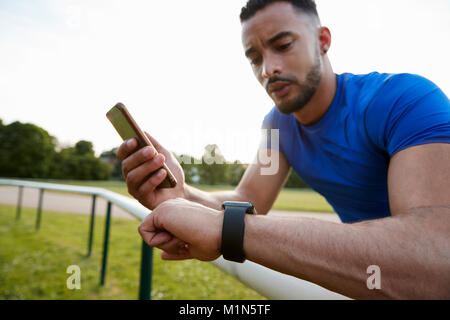 Male athlete using fitness app on smartphone and smartwatch - Stock Photo