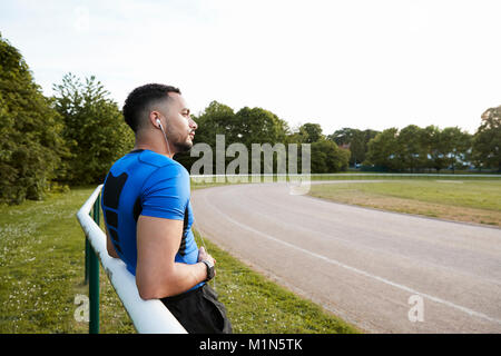 Male athlete wearing earphones taking a break at a track - Stock Photo