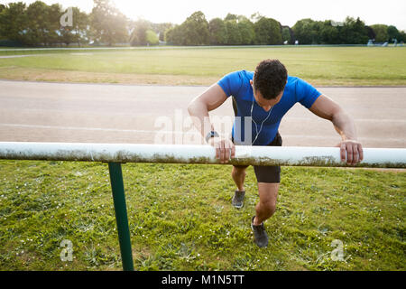 Male athlete stretching at running track, close up - Stock Photo