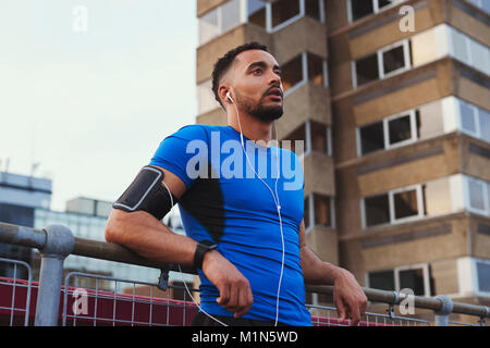 Male runner takes a break leaning on fence in urban setting - Stock Photo