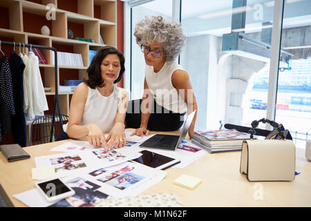 Two female creatives discussing magazine layout in an office - Stock Photo