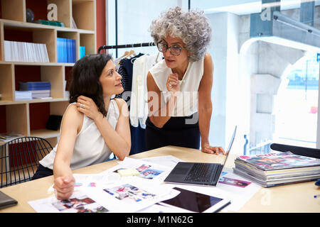Two female creatives discussing magazine layout, close up - Stock Photo