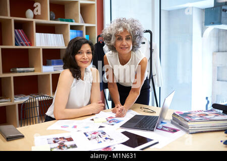 Two female creatives working in office looking to camera - Stock Photo