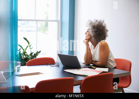Middle aged woman looking out of the window in the boardroom - Stock Photo