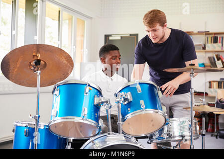 Male Pupil With Teacher Playing Drums In Music Lesson - Stock Photo