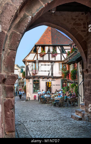 RIQUEWIHR Stone medieval arched entrance to Riquewihr an historic popular floral village with restaurants and bars - Stock Photo