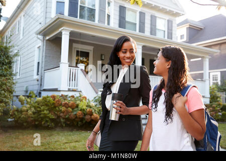 Businesswoman Mother Walking Daughter Back From School - Stock Photo