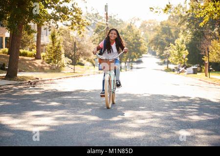Girl Riding Bike Along Street To School - Stock Photo