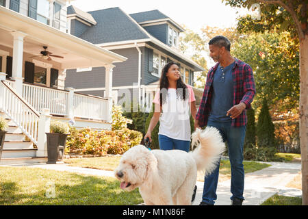 Father And Daughter Walking Dog Along Suburban Street - Stock Photo