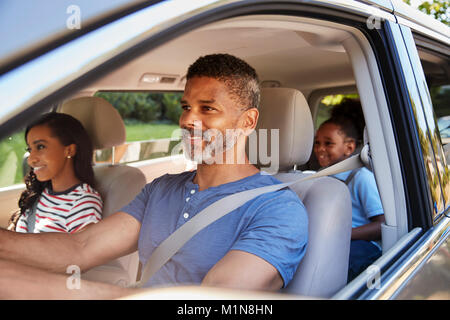 Family In Car Going On Road Trip - Stock Photo