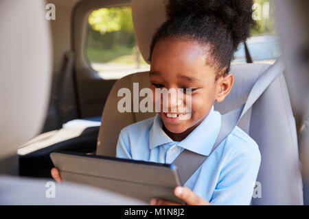 Boy Using Digital Tablet On Car Journey - Stock Photo
