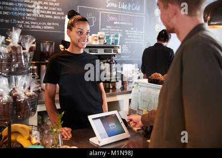 Customer Paying In Coffee Shop Using Credit Card - Stock Photo