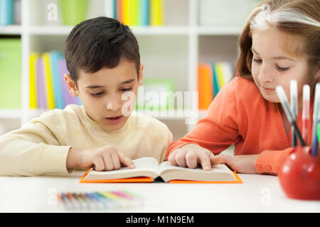 young brother and sister learn how to read - Stock Photo