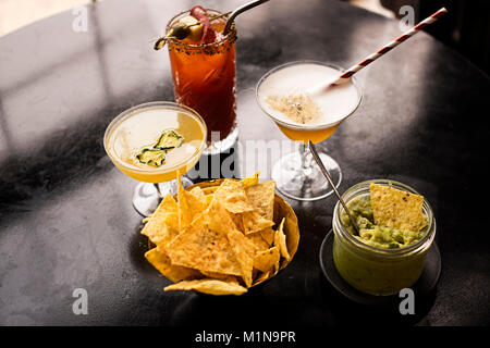 Trio of classic cocktails served with tortilla chips and guacamole. - Stock Photo