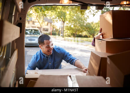 Couple Unloading Boxes From Van On Family Moving In Day - Stock Photo