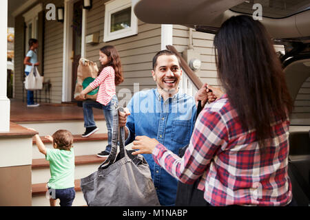 Family Unloading Shopping Bags From Car - Stock Photo