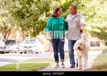 Senior Couple Walking Dog Along Suburban Street - Stock Photo