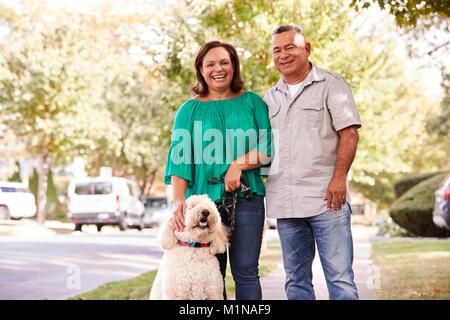 Portrait Of Senior Couple Walking Dog Along Suburban Street - Stock Photo