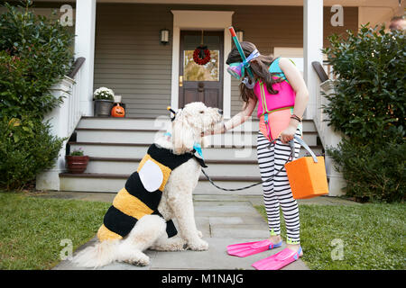 Girl With Dog Wearing Halloween Costumes For Trick Or Treating - Stock Photo