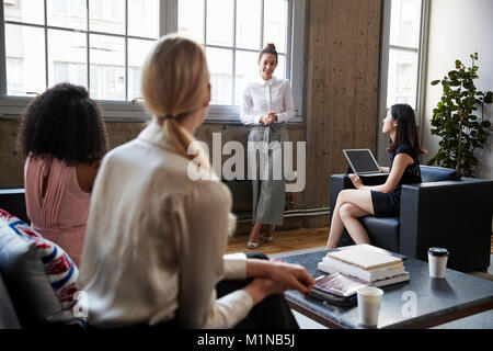 Standing female manager talking to team at casual meeting - Stock Photo