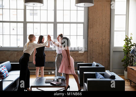 Female colleagues high five at a motivational meeting - Stock Photo
