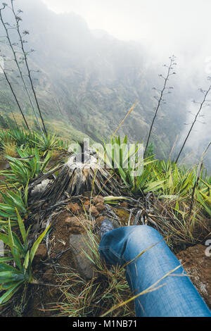Leg of traveler staying on the ledge above the foggy green valley overgrown with agaves Santo Antao island in Cabo - Stock Photo