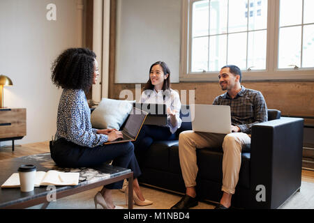Smiling work colleagues with laptops at a casual meeting - Stock Photo