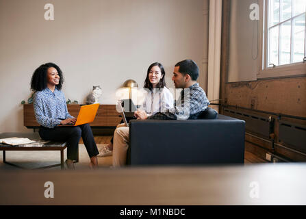 Smiling work colleagues using laptops at a casual meeting - Stock Photo