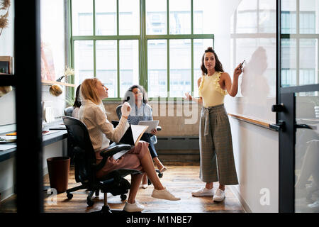 Woman looking to whiteboard in a meeting with female team - Stock Photo