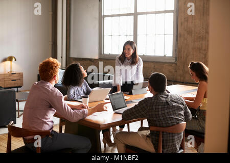 Smiling woman standing to address colleagues at a work meeting - Stock Photo