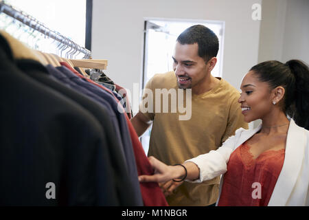 Young Hispanic couple looking at clothes in a clothes shop - Stock Photo