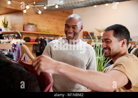 Two male friends look at clothes in a clothes shop, close up - Stock Photo
