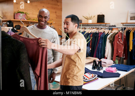 Two male friends looking at clothes in a clothes shop - Stock Photo