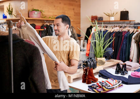 Young Hispanic man looking at clothes in a clothes shop - Stock Photo