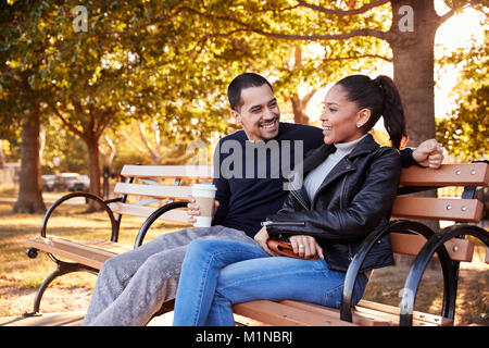 Young Hispanic couple sitting on bench in Brooklyn park - Stock Photo