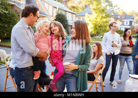 Parents holding their young kids while they eat at a block party - Stock Photo