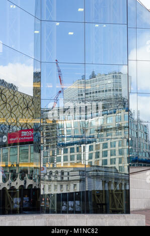 The new Library of Birmingham in Centenary Square reflected in glass windows of Symphony Hall and the International - Stock Photo
