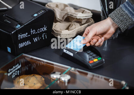 Customer is paying with contactless credit card in shop. - Stock Photo