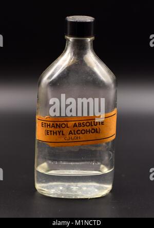 Retro scientific ethyl-alcohol bottle with orange label on a seamless black background. - Stock Photo