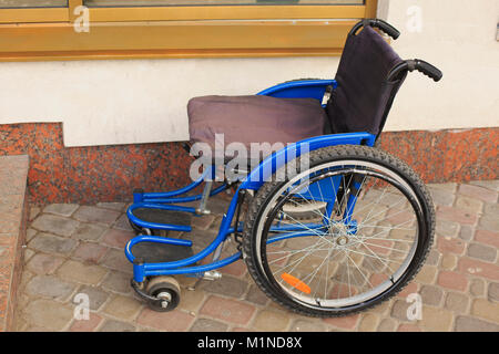 Empty wheelchair next to a shop on the street. - Stock Photo