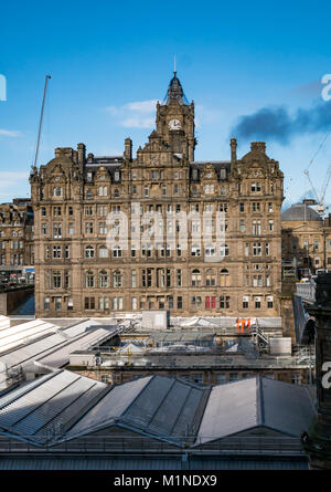 Rocco Forte Balmoral Hotel, Princes Street, Edinburgh, UK, with Waverley Station roof in front, and blue sky, cranes - Stock Photo