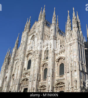 Front of the Main Cathedral In Milan Italy Highlighting the Vertical Spires and Stone Facade of the Building - Stock Photo