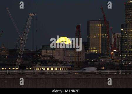 London, UK. 31st Jan, 2018. A blue super moon rises over the City of London. Seen from Hungerford Bridge in London. - Stock Photo